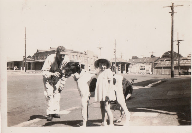 A man dressed in overalls stands with his arm outstretched to a very large dog as if to keep it still.  The dog is as tall as a little girl Barbara aged 5 standing next to it with her arm resting on its back.  The photo is taken in front of what looks like a petrol station and garage.