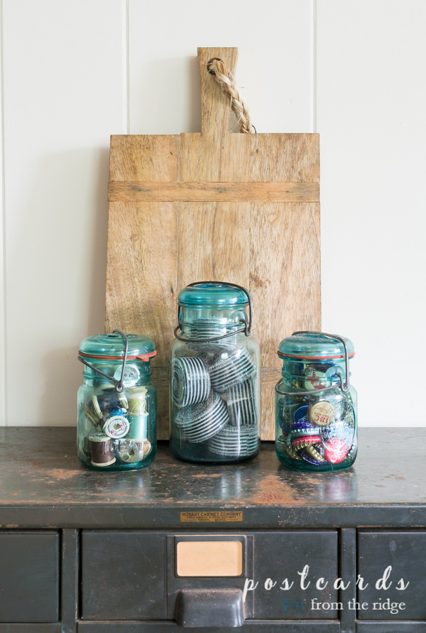 wooden cutting board and blue mason jars with ribbons, thread, and bottle caps