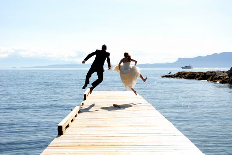 Newly married couple jumping for joy