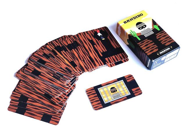 na zdjęciu pudełko od gry Bandido, obok pudełka leży rozłożona w rządku talia kart a na pierwszym planie karta z wizerunkiem przestepcy