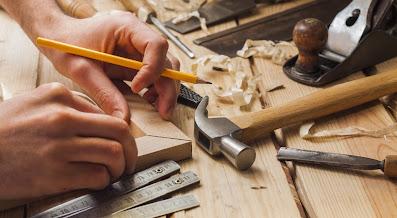 نجار متخصص معه أدواته يقوم بضبط زاوية برواز خشبي