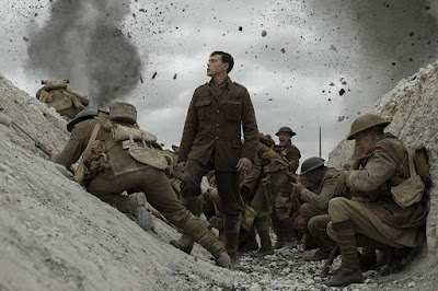 "In ""1917,"" George MacKay stands near an explosion in a trench with other soldiers as they prepare to run into battle."