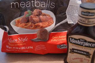 A bag of froze meatballs along side a bottle of BBQ sauce.