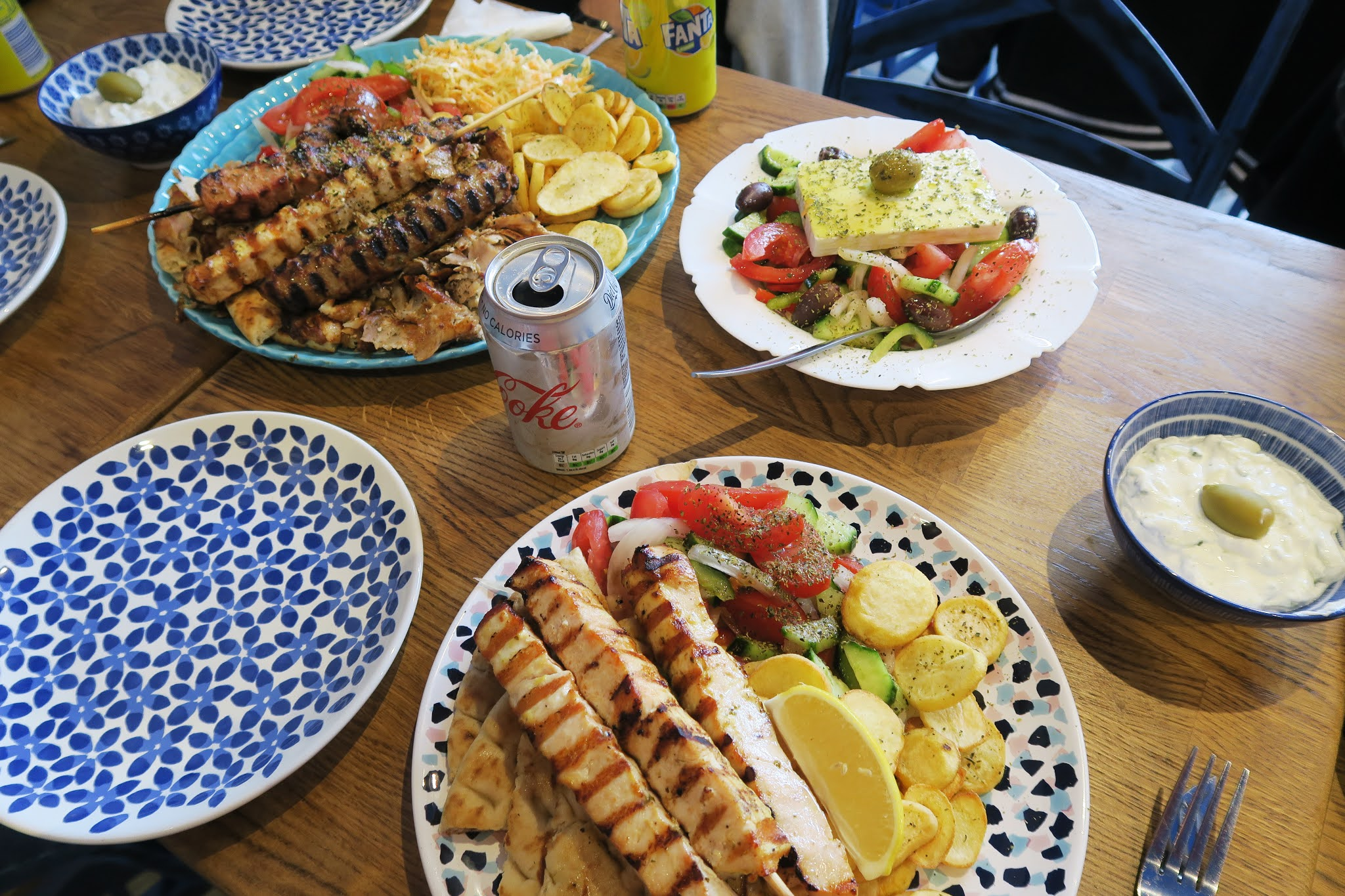 A plate of Chicken Souvlaki, a mixed grill,  a bowl of salad, and a bowl of Tzatziki at Mr Souvlaki Restaurant Stourbridge
