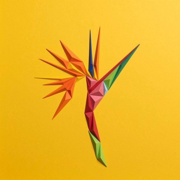 vivid bird of paradise flower composed of folded paper triangles on yellow background