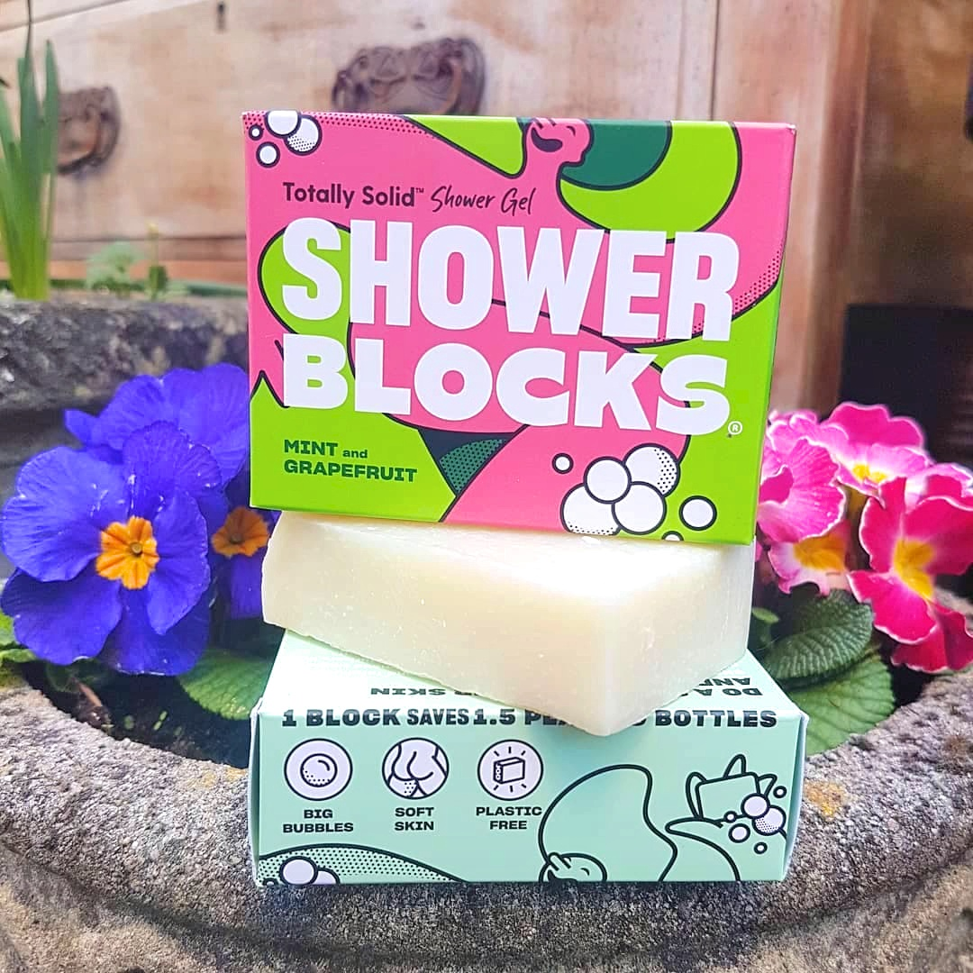 Shower Blocks plastic free shower gel soap bars stacked up next to purple and pink  primroses