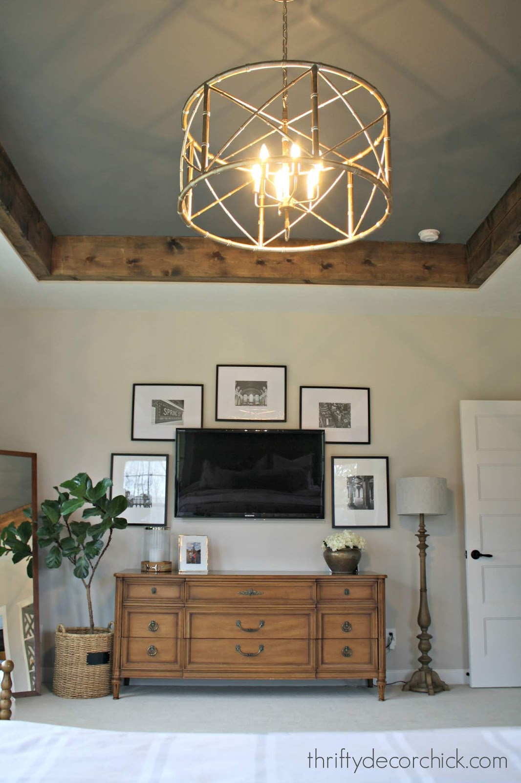 Cozy master with dark gray tray ceiling and wood beams