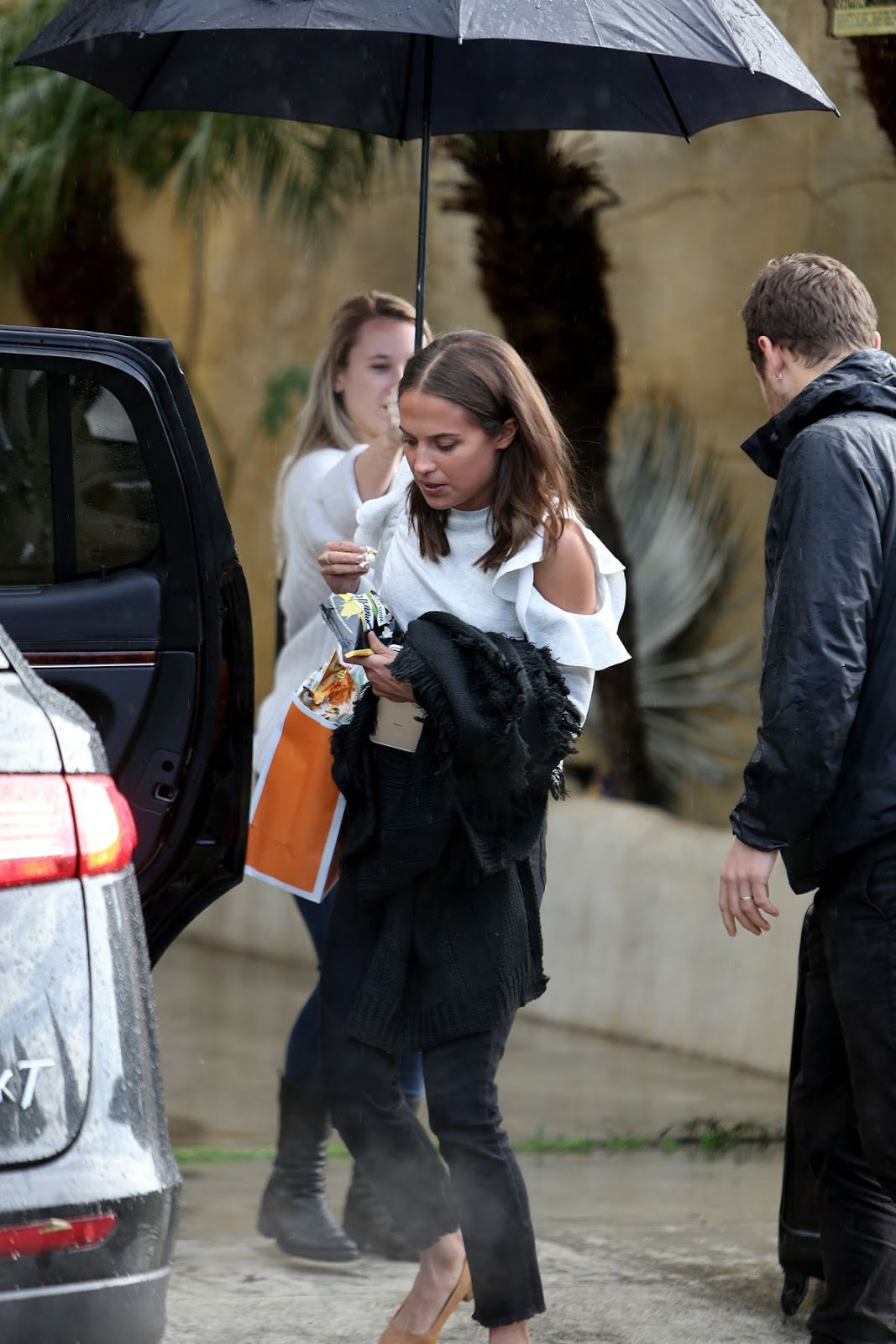 Alicia Vikander leaves her car in heavy rain In Venice Beach