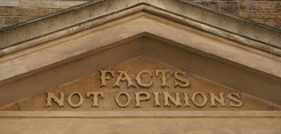 Photograph of a triangular stone pediment, inside which are the words 'Facts not opionions' in embellished Victorian lettering.