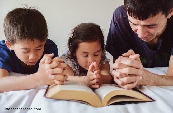 Padre ora con sus hijos antes de leer la Biblia