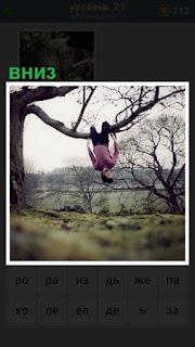 на ветке дерева висит вниз головой мужчина
