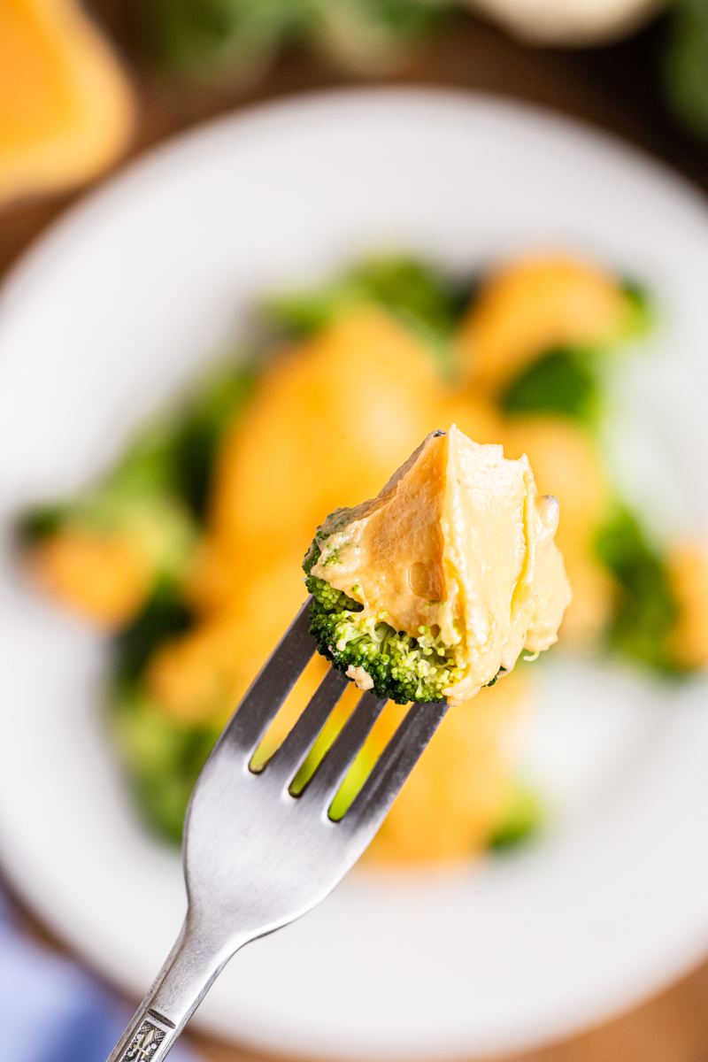 Close up photo of a broccoli floret on a fork coated with Easy Keto Cheese Sauce.
