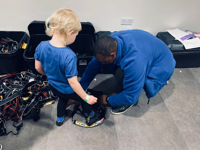 A 4 year old getting a full body harness on ready to go climbing