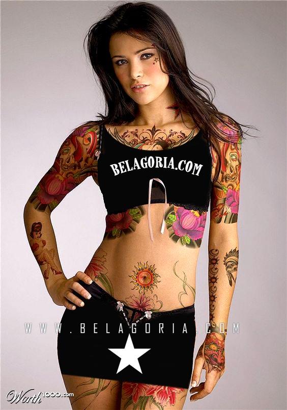 vemos a una preciosa modelo posando de pie lleva tatuaje solar en el ombligo