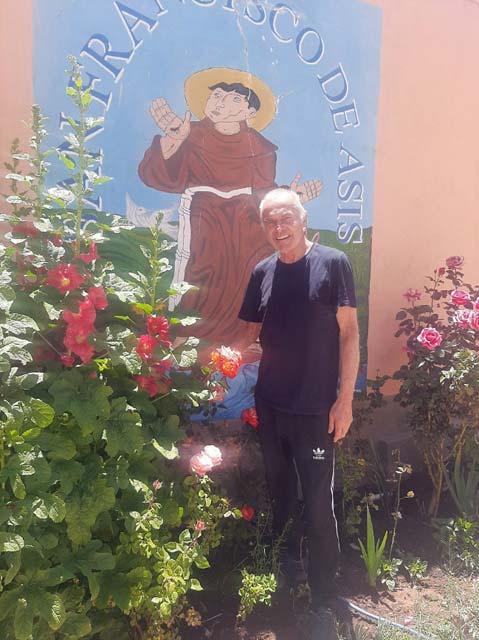 Foto: Der Padre vor dem Bild des heiligen Franziskus welches von Blumen gesäumt ist
