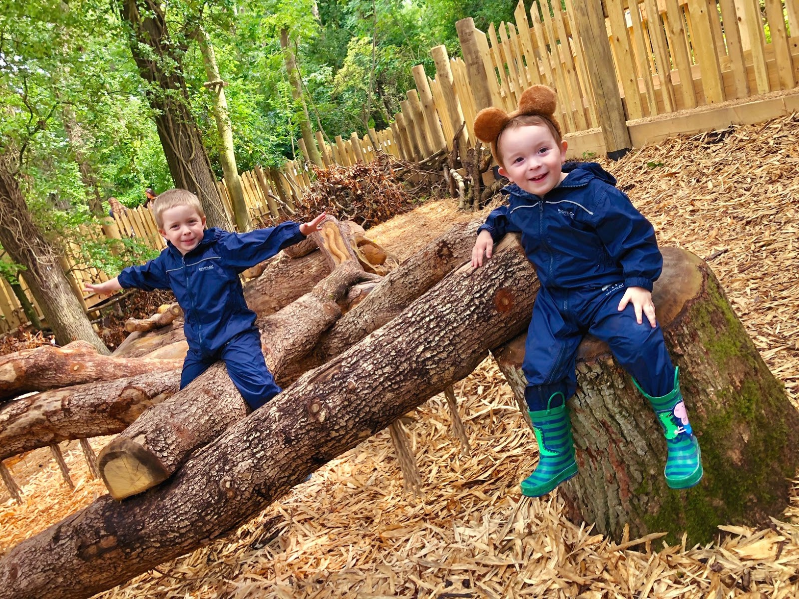 two boys wearing puddle suits and sitting on logs in the woodland at wild place project