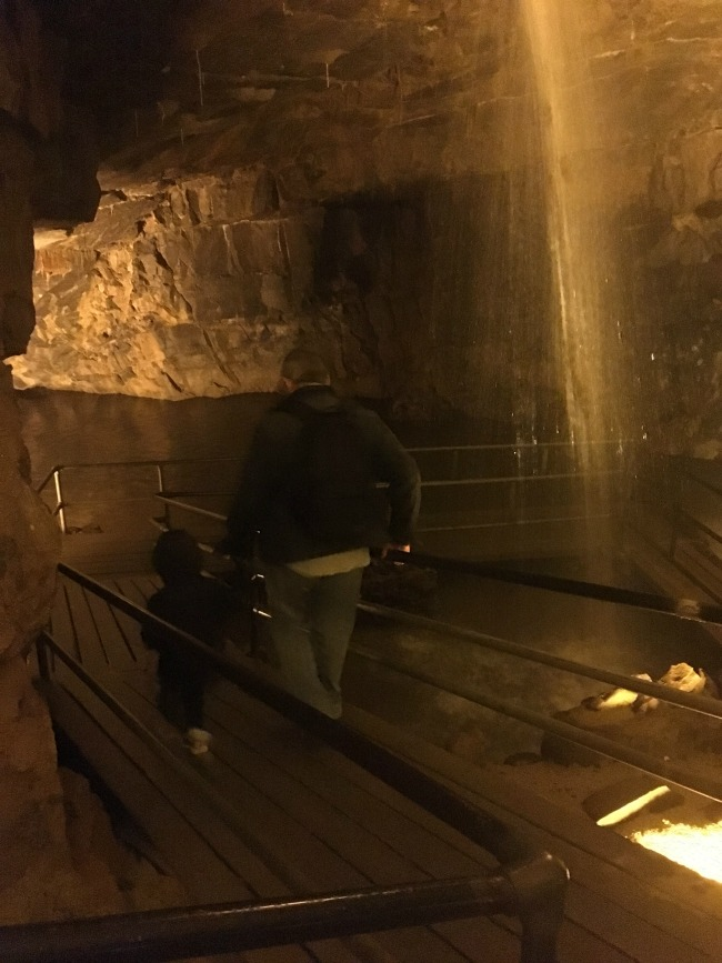 man-and-boy-inside-cathedral-cave-with-water-pouring-down-at-dan-yr-ogof
