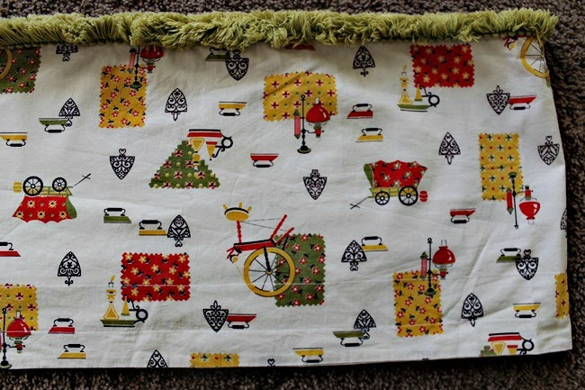 vintage novelty print kitchen curtain fabric with irons, wagons, fabric and spinning wheels
