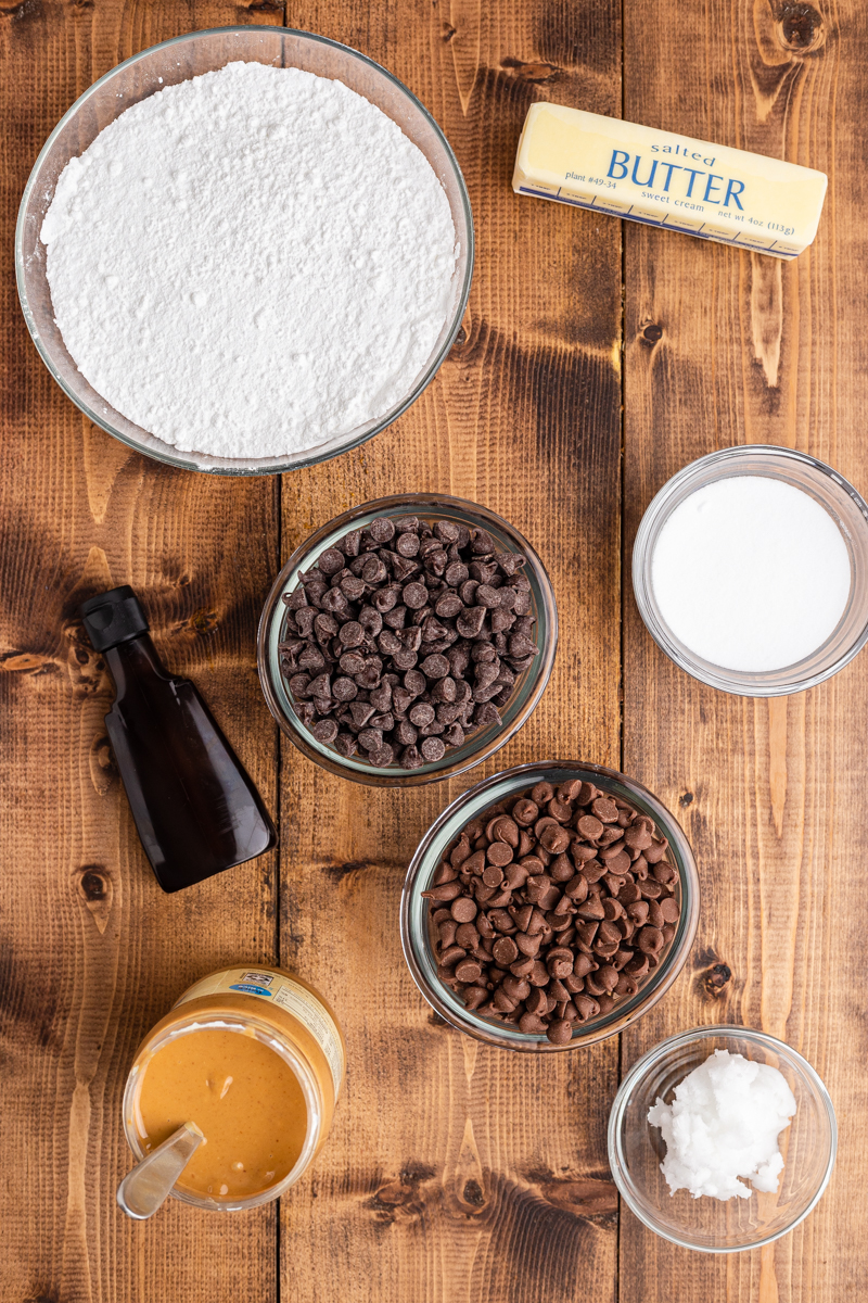 Overhead shot of the ingredients needed to make Keto Peanut Butter Chocolate Easter Eggs on a wooden table.