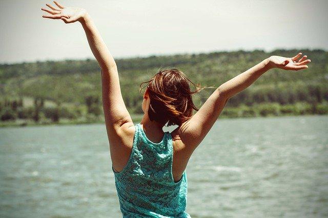 Wanita berdiri dengan mengangkat tangan yang mendandakan kebahagiaan