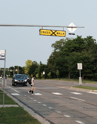 A pedestrian cautiously crossing Plymouth Rd at a mid-block crosswalk