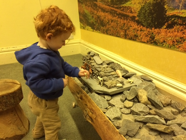 Toddler playing toy farm animals at a wooden table, covered in rocks