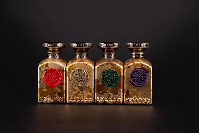 Zdjęcie flakonów perfum. Flakony sa pokryte złotem i każdy ozdoviony jest pieczęcią z laku