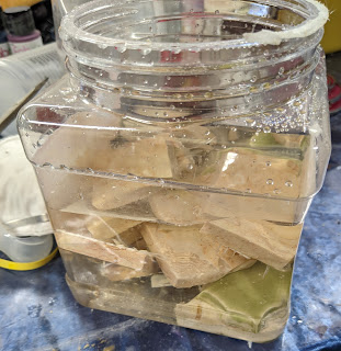 Plastic jar full of marble pieces, tiles, and sugar water