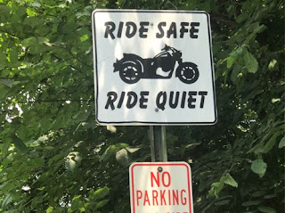 Ride Safe, Ride Quiet sign along roadside.