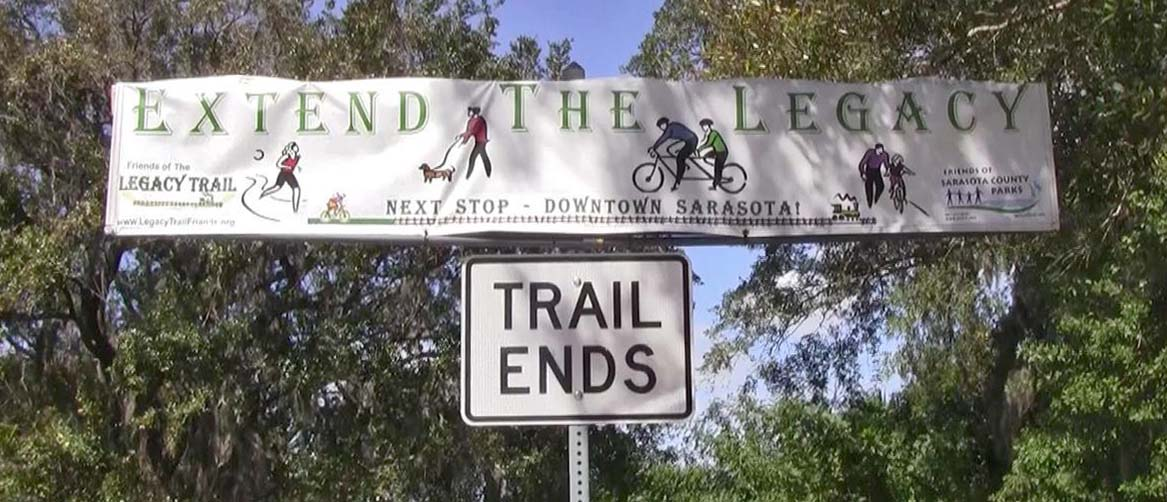 Two signs hanging on trees say trail ends and extend the Legacy Trail sign in Sarasota, Florida.