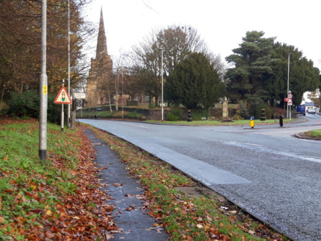 A view of the main road into Winwick from the footpath.  The church is ahead, surrounded by trees, and there is a road that goes off to the right
