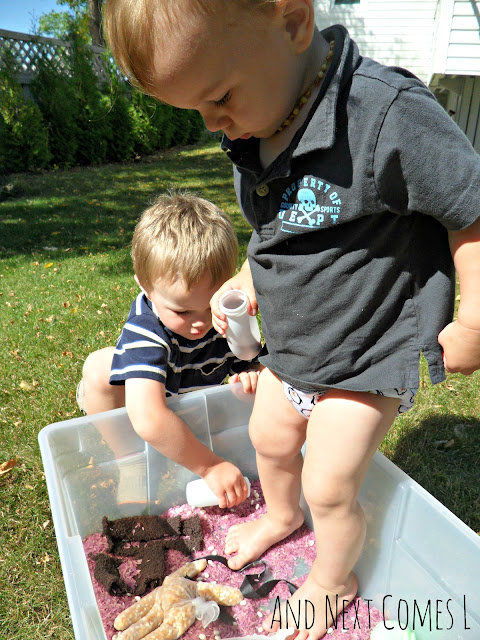 Toddler standing in a Gruffalo sensory bin with dyed rice