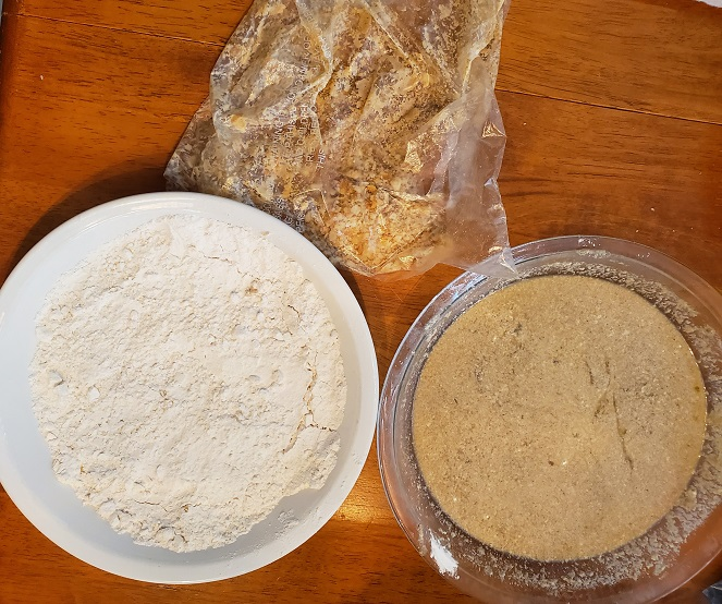 these are the ingredients use to make homemade chicken tenders, there is flour in a pie plate along with bread crumbs and a baggies to share the chicken in