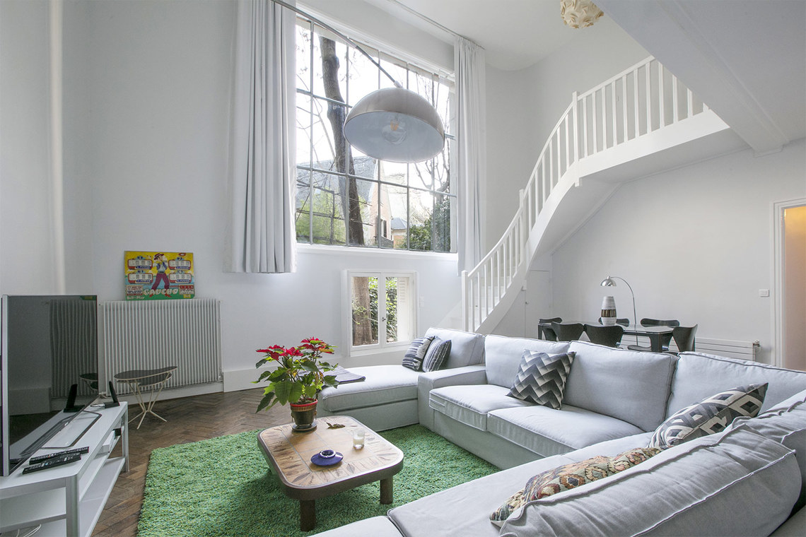 Sectional sofa in living room with huge picture window of Paris apartment on Avenue Frochot seen on Hello Lovely Studio