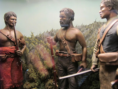 Diorama of 19th-century Maori with muskets in the bush.