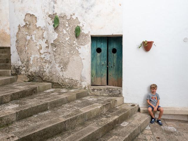 Niño sentado en una escalera junto a una puerta turquesa con fachada desconchada en Specchia con cactus
