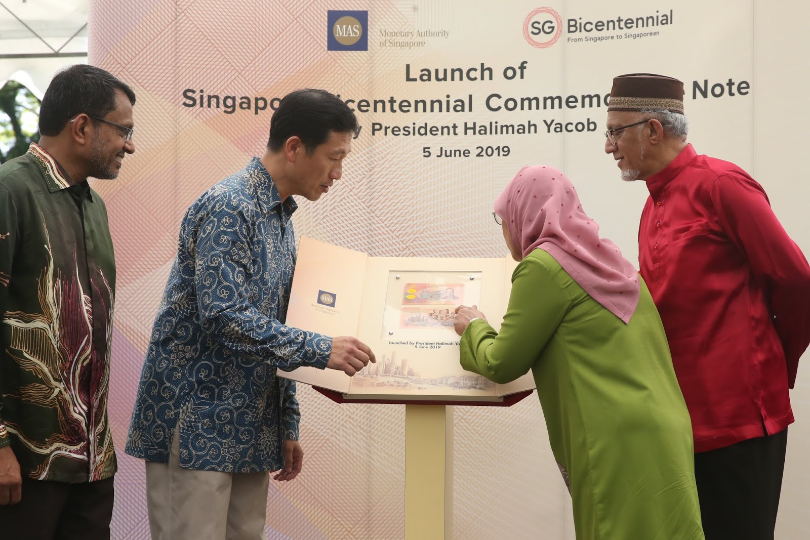 President Halimah Yacob and Minister for Education Ong Ye Kung look at the Singapore Bicentennial commemorative note after launching it at the Istana Open House on Hari Raya Puasa (June 5).
