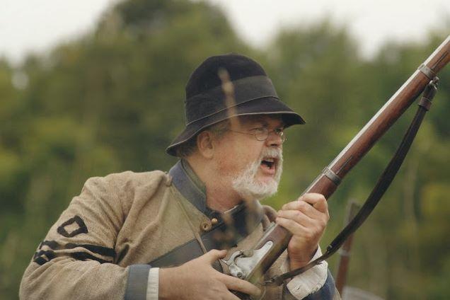 elderly man holding a rifle shouting