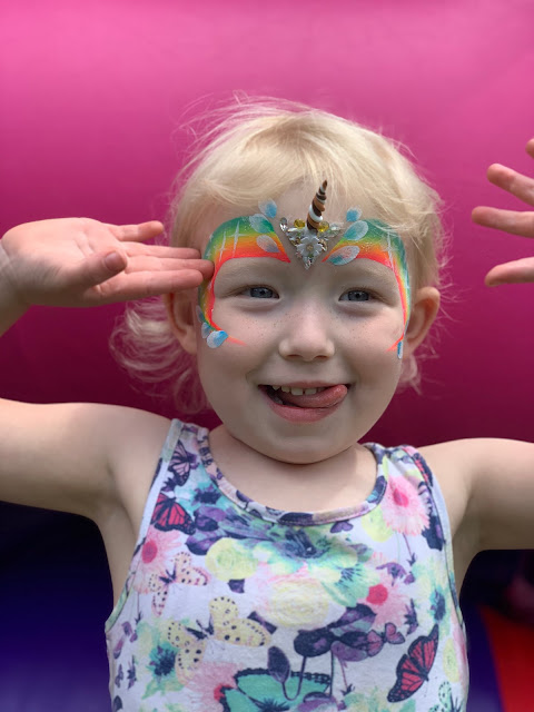 A toddler with a unicorn rainbow facepaint and sticker with a 3d horn on