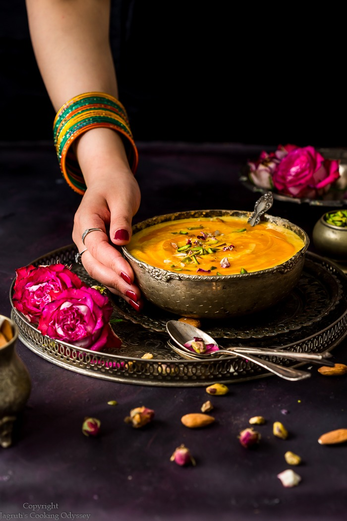 A girl is holding a bowl of mango kheer in her hand with a spoon.