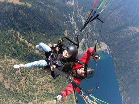 Two people tandem paragliding high over Wallowa Lake