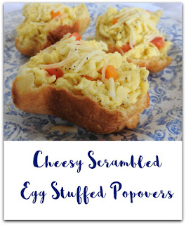 cheesy scrambled eggs in popovers on blue and white plate