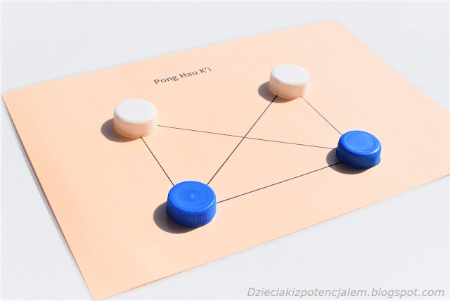 na zdjęciu plansza do gry w Pong Hau Ki, która składa się z siedmiu linii , na których przecięciach znajdują się punkty ustawienia pionów, na planszy pozycja początkowa czyli dwa białe piony w dwóch górnych rogach planszy, dwa niebieskie piony w dolnych rogach a środkowe pole pozostaje puste.
