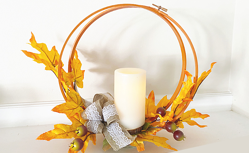 embroidery hoop centerpiece with leaves and a candle
