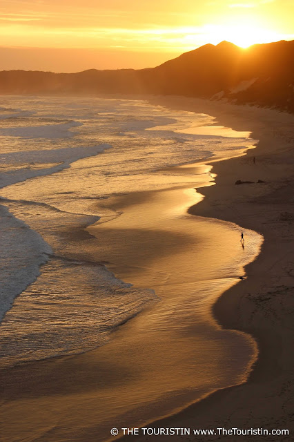 A golden sunset; people walking in the sunset's reflection on the beach in Brenton-on-sea in South Africa