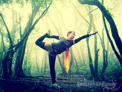 Woman doing yoga in the mountain with fog
