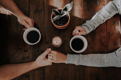 Pareja tomada de la mano mientras toman un café