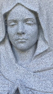 A close-up detail of the face of a marble statue of the Virgin Mary in Greenwood Cemetery, Brooklyn