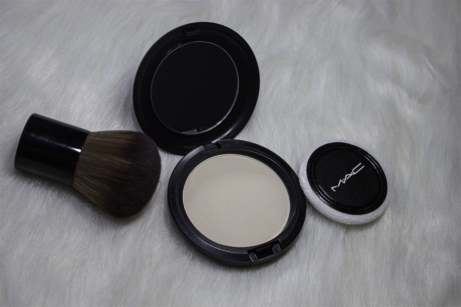 a close up picture of mac cosmetics lot powder that lays on a fluffy rug