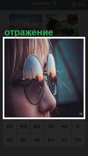 на лице девушки одеты очки, в которых отражение действительности